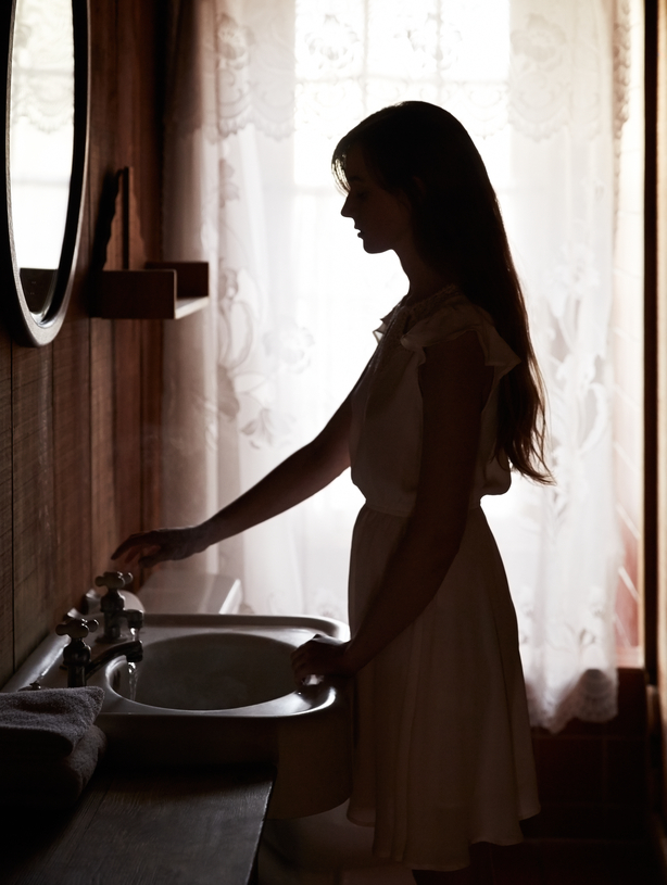 Silhouetted woman using sink in bathroom
